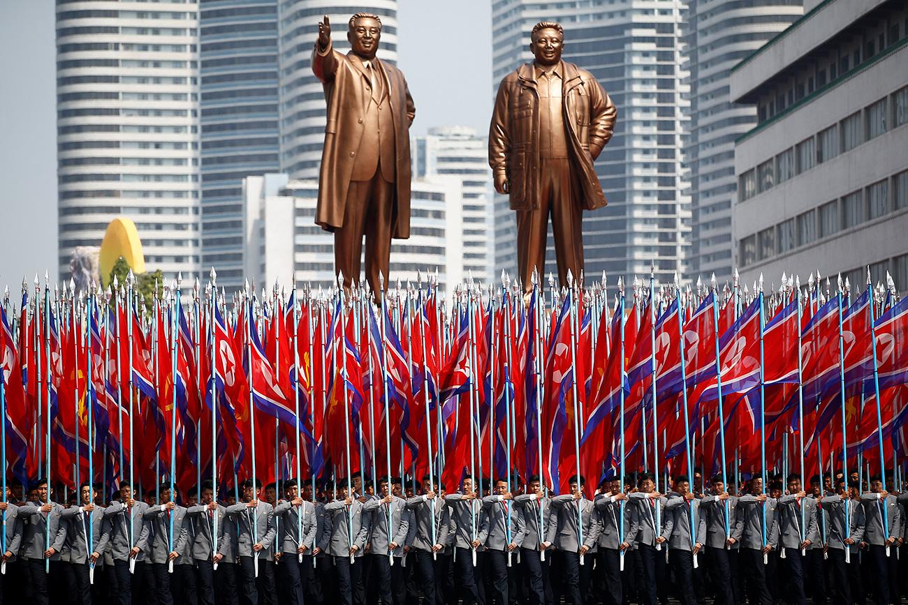 Ljudi nose zastave Sjeverne Koreje ispred kipova Kim Il Sunga i Kim Jong Ila, na vojnoj paradi povodom 105. godina od rođenja Kim Il Sunga.