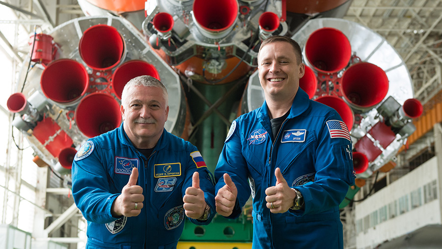 "Fyodor Yurchikhin and Jack Fischer give a ""thumbs up"" in front of the Soyuz rocket."