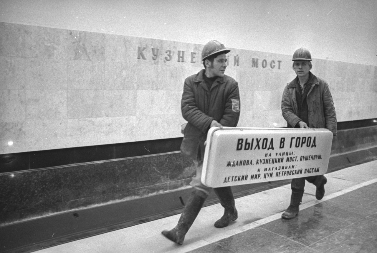 "Builders carry a ""Way Out"" sign at Kuznetsky Most subway station, 1973    Over his fifty years of service for Izvestia, he received every prize and accolade in the business, including the national award ""Golden Eye of Russia"" and the international competition World Press Photo (four-time winner)."
