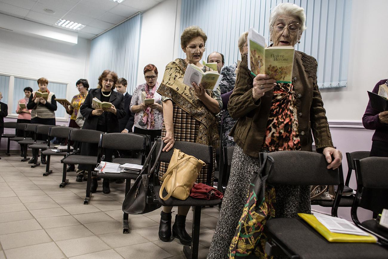 Selama kebaktian, para jemaahnya mendengarkan khotbah dan ajaran Yehuwa dan juga bernyanyi. Sumber: Getty Images
