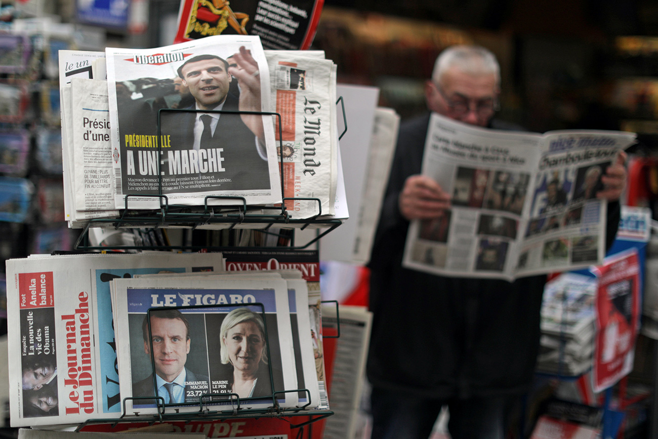 A man reads the local newspaper near a rack which displays copies of French daily newspapers with front pages about the results in France's Presidential election in Nice, France, April 24, 2017.