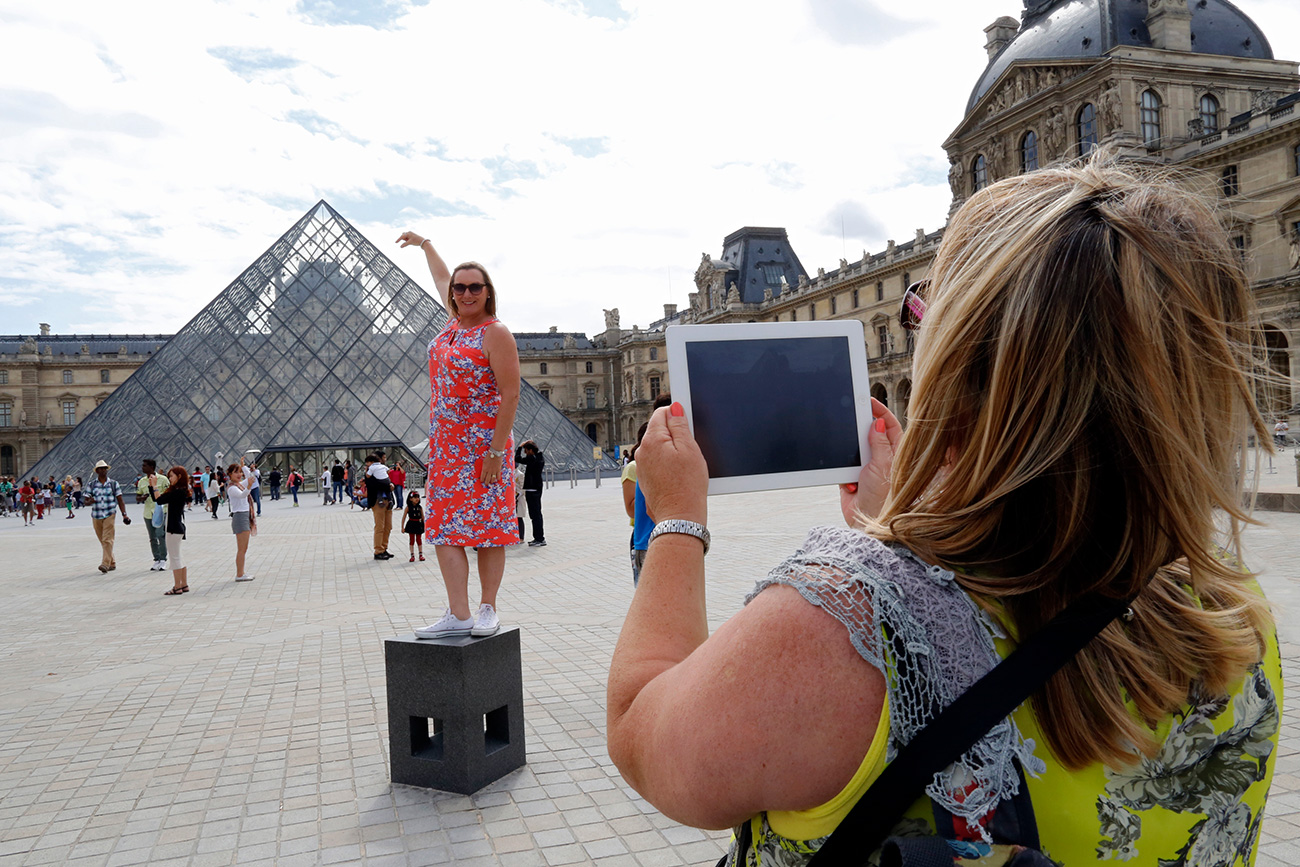 "Ahead of the holiday season, the Russian MFA updated its recommendations on how not to offend the locals, how not to end up in jail, and how not to earn the reputation of a ""bad Russian."" Photo: A tourist poses for a souvenir picture near the Pyramid of the Louvre Museum in Paris."