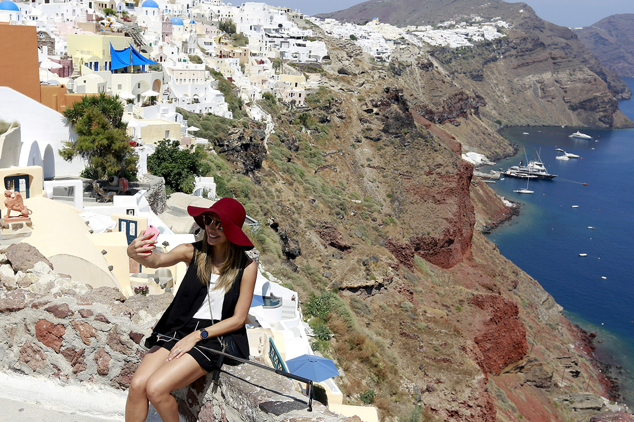 The most popular destinations included Minsk (+117 percent), Yerevan (+84 percent) and Tbilisi (+52 percent). Photo: A tourist takes a selfie in the village of Oia on the Greek island of Santorini, Greece.