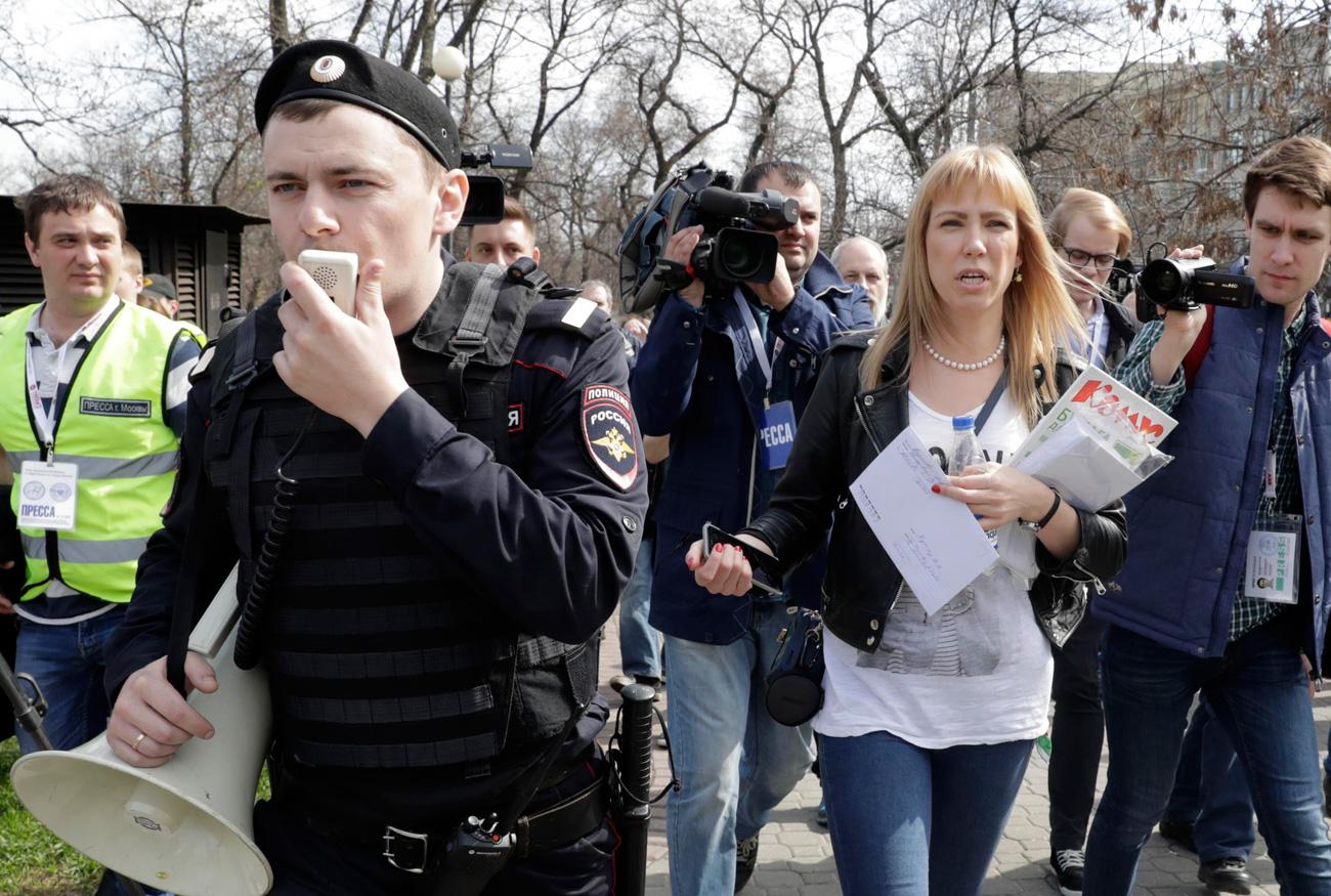 Coordinatrice du mouvement Open Russia, Maria Baronova (deuxième à droite) entourée de journalistes et de représentants des forces de l'ordre.n