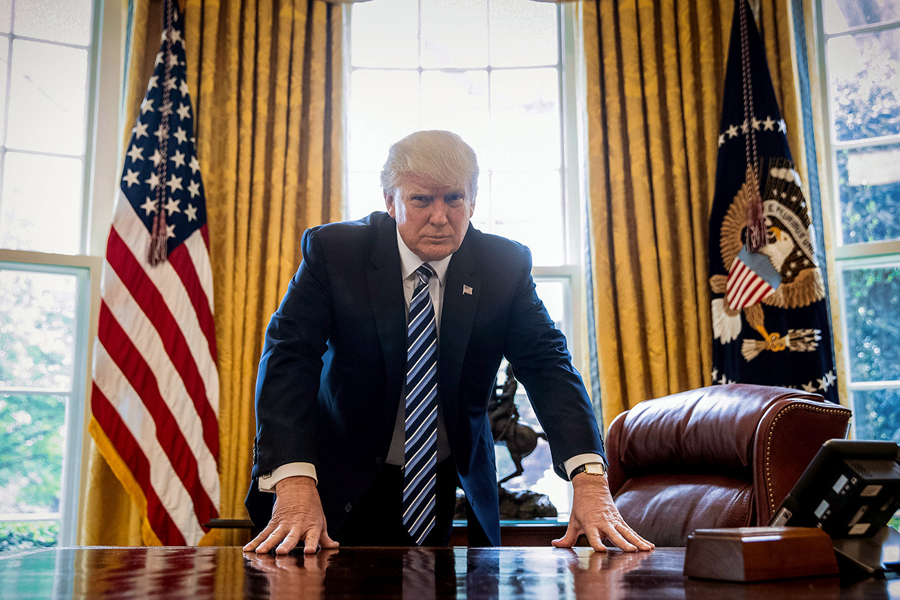 President Donald Trump poses for a portrait in the Oval Office in Washington, April 21, 2017.