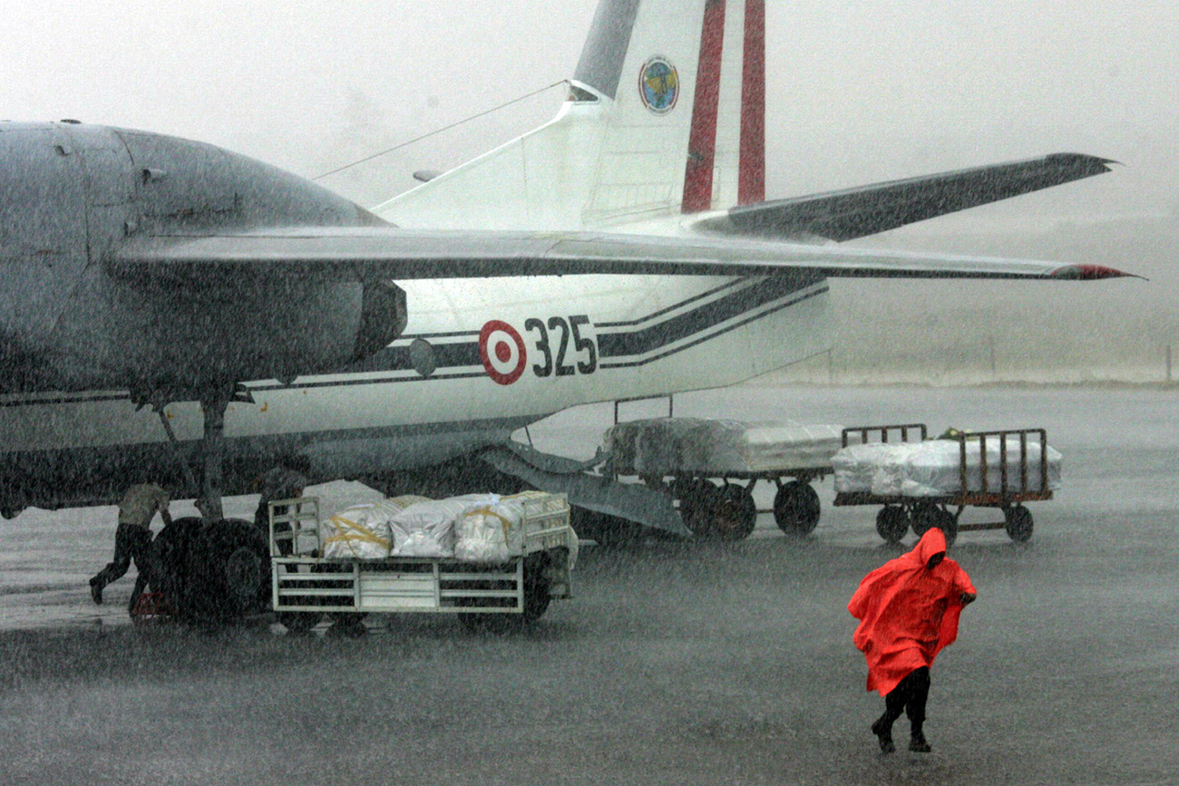Coffins of Tans Peru airline Boeing 737-200 victims weating to be send to Lima under heavy rain at the tarmac of the Pucallpa's airport before, August 2005. AFP