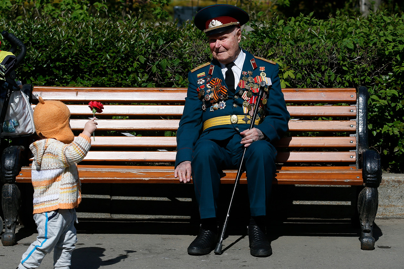 A little girl gives a flower to a blind World War Two veteran during the Victory Day celebrations at Gorky park in Moscow, Russia, May 9, 2015