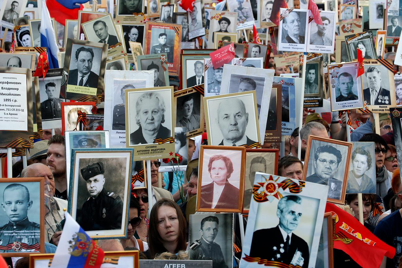5月9日、ロシアの多くの街で、戦争に参加した親族の写真を持ちながら、数千人の人々が通りを歩く。=