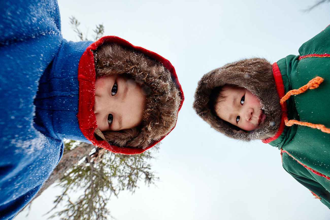 Directly below view of the Nenets kids in fur hats looking at camera against sky background, Yamal peninsula, Russia