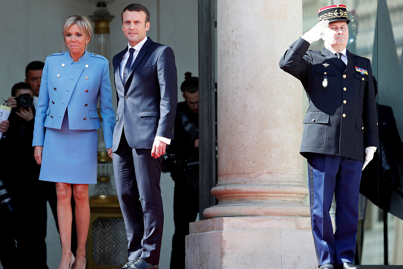 French President Emmanuel Macron and his wife Brigitte Trogneux stand on the steps of the Elysee Palace as former President Francois Hollande (not pictured) leaves after the handover ceremony in Paris, France, May 14, 2017. Source: Reuters