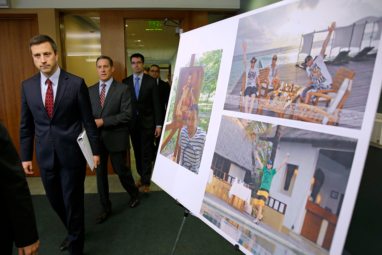 Trevor McFadden, left, acting principal deputy assistant attorney general, and other officials walk past photos of Russian hacker Roman Seleznev as they arrive to talk to reporters on April 21, 2017, following the federal court sentencing of Seleznev to 27 years in prison after he was convicted of hacking into U.S. businesses to steal credit card data. Source: AP