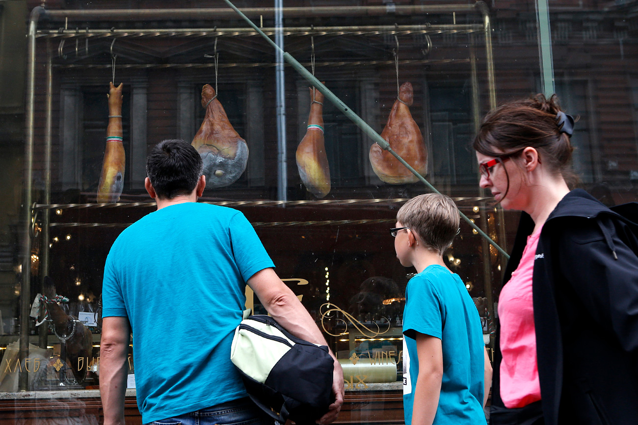 More than a half of Russian citizens support restrictions that Moscow imposed on food imports in response to Western sanctions. Photo: People pass by a shop window displaying Spanish ham for sale at a grocery store in St. Petersburg.