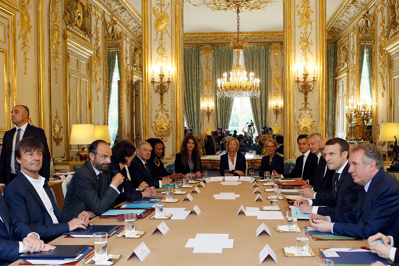 Francoski predsednik Emannuel Macron sedi nasproti premierja Edouarda Phillipea (drugi z leve) med prvim srečanjem novega kabineta ministrov v pariški Elizejski palači v Franciji, 18. maj 2017. Na srečanju sta bila tudi minister za pravosodje Francois Bayrou ter minister za okoljevarstvo (desno) in tranzicijo Nicholas Holut (levo). Vir: Reuters