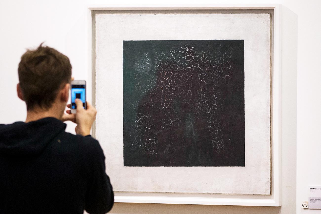Seorang pria mengambil gambar 'Persegi Hitam', sebuah mahakarya oleh seniman 'avant-garde' Rusia Kazimir Malevich, di Galeri Tretyakov Moskow.