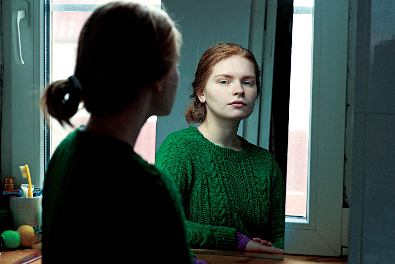 Beautiful red-haired girl looking at the mirror. Russia