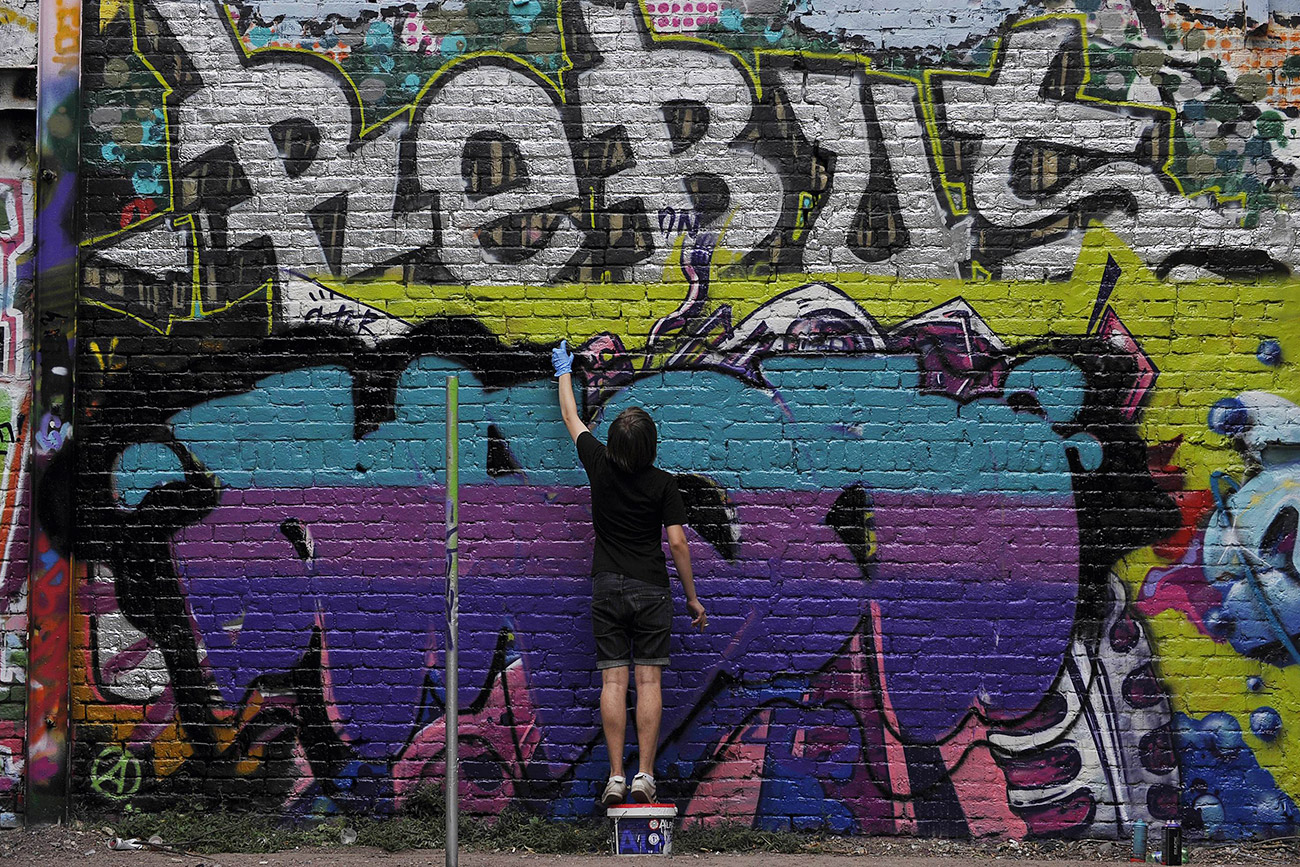 Ruski najstnik na zid v Moskvi riše grafit. / Fotografija: AFP