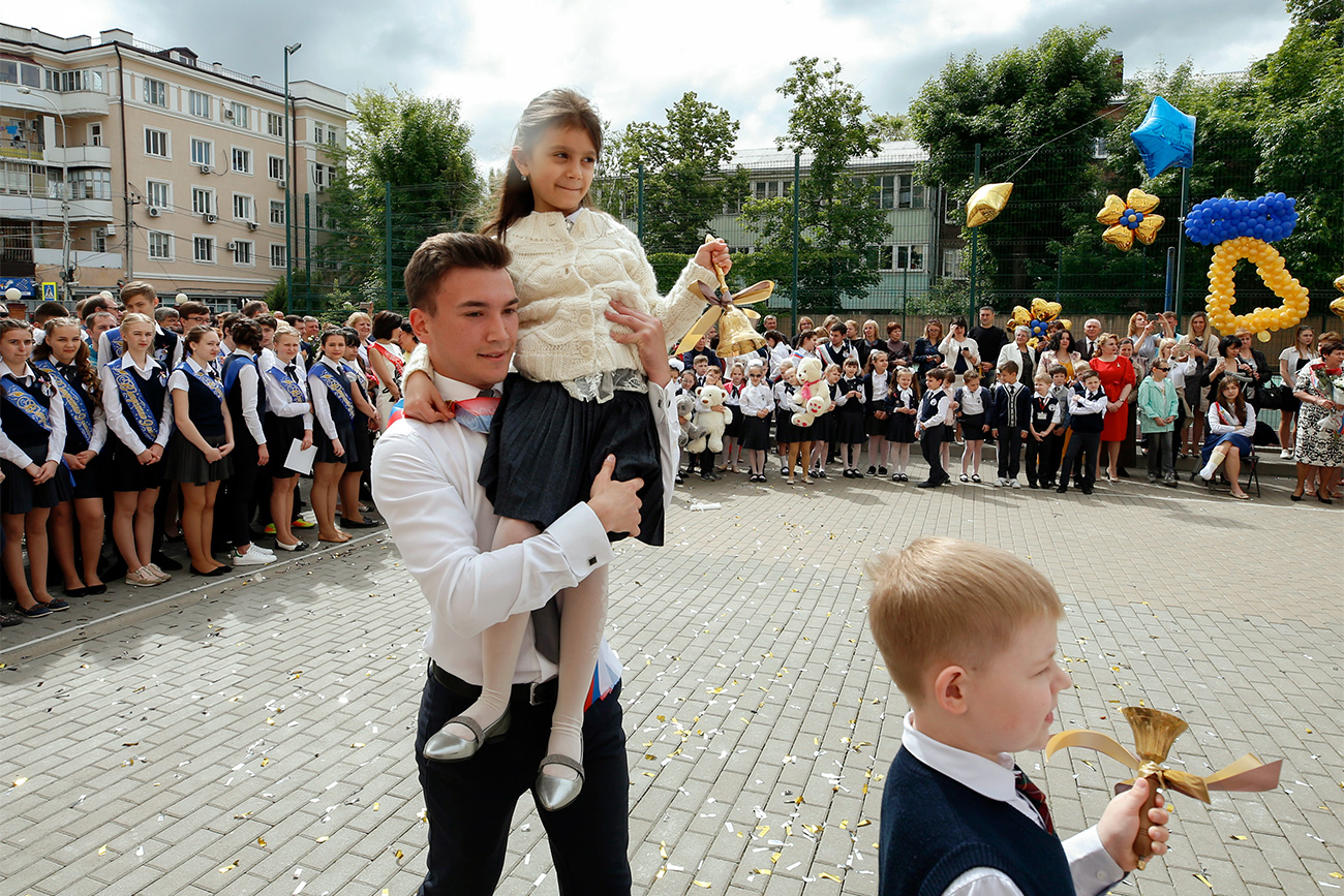"""In Russia, this coming-of-age moment is known as the """"Last Bell"""". It traditionally involves the heftiest final-year student carrying on their shoulders the prettiest first-grader, who rings a large bell."""