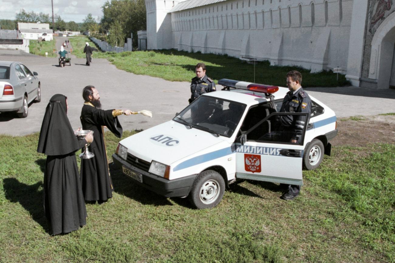 Отац Александар из Толшког манастира (Јарославска област) прска светом водом сараднике полиције и нови патролни аутомобил. 1999.