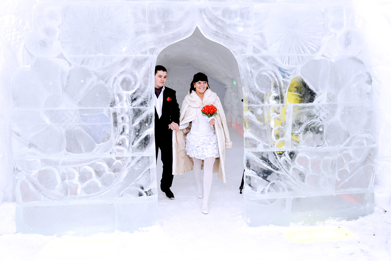 MURMANSK REGION, RUSSIA. FEBRUARY 29, 2012. Newly weds at an Ice Wedding Palace built as part of the Snow Village at the foothills of the Khibiny Mountains, near Kirovsk.