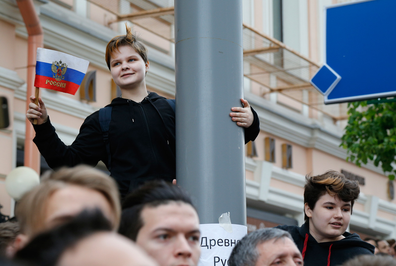 A young protestor holds up a Russian flag during a demonstration in downtown Moscow, Russia, Monday, June 12, 2017. Russian opposition leader Alexei Navalny, aiming to repeat the nationwide protests that rattled the Kremlin three months ago, has called for a last-minute location change for a Moscow demonstration that could provoke confrontations with police