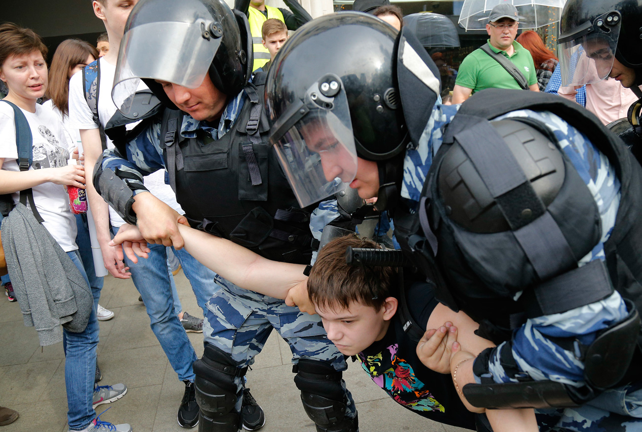 A young demonstrator is apprehended by riot police during a demonstration in downtown Moscow, June 12, 2017. / AP