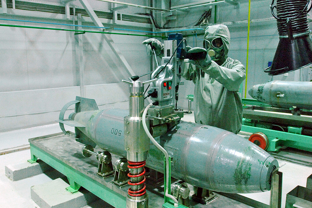 An employee wears a gas mask and suit as he works at the chemical air weapons destruction facility at the Settlement of Maradykovo, Kirov Region.