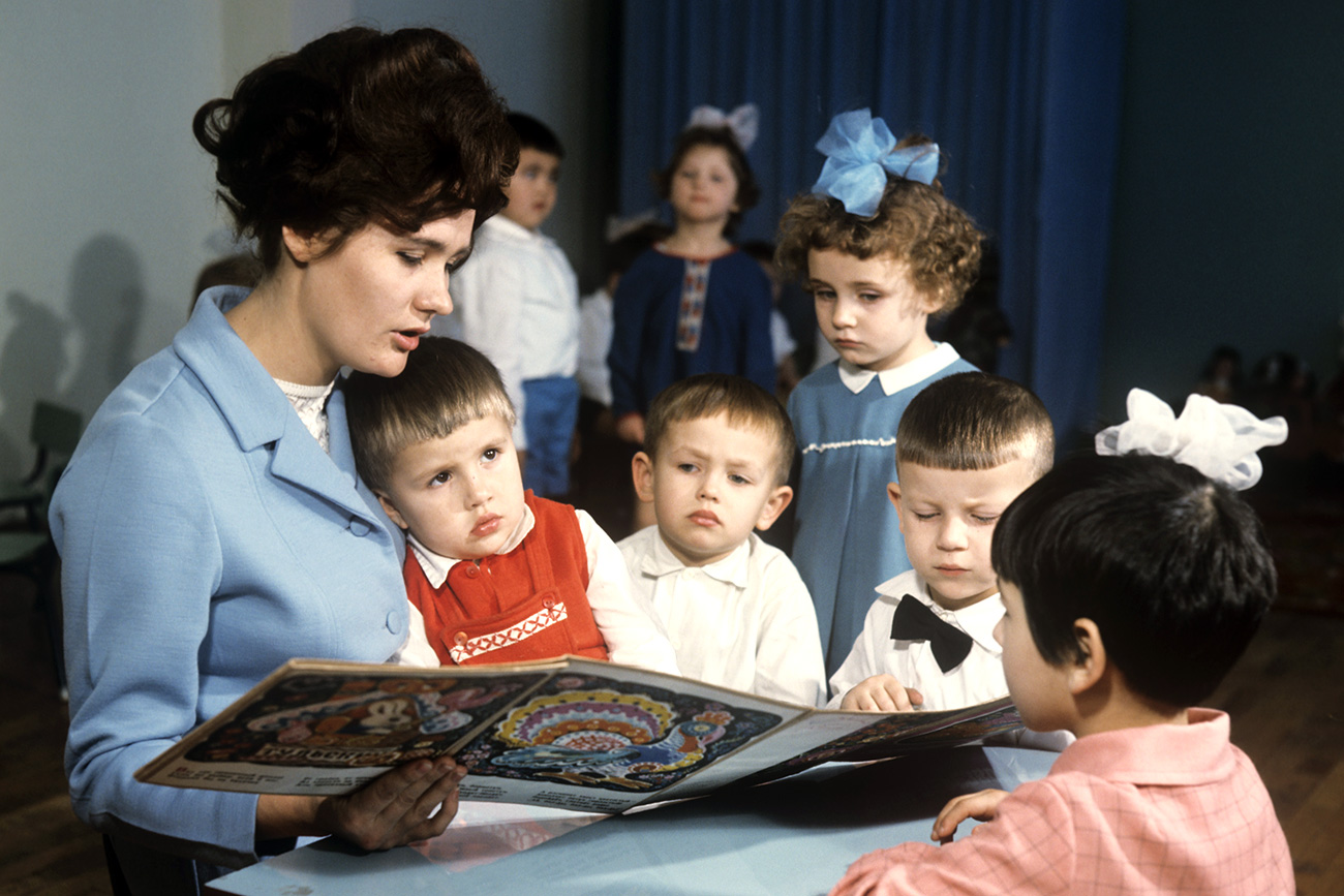 """Professora lê para crianças no jardim de infância da fábrica soviética """"Kolosok""""."""