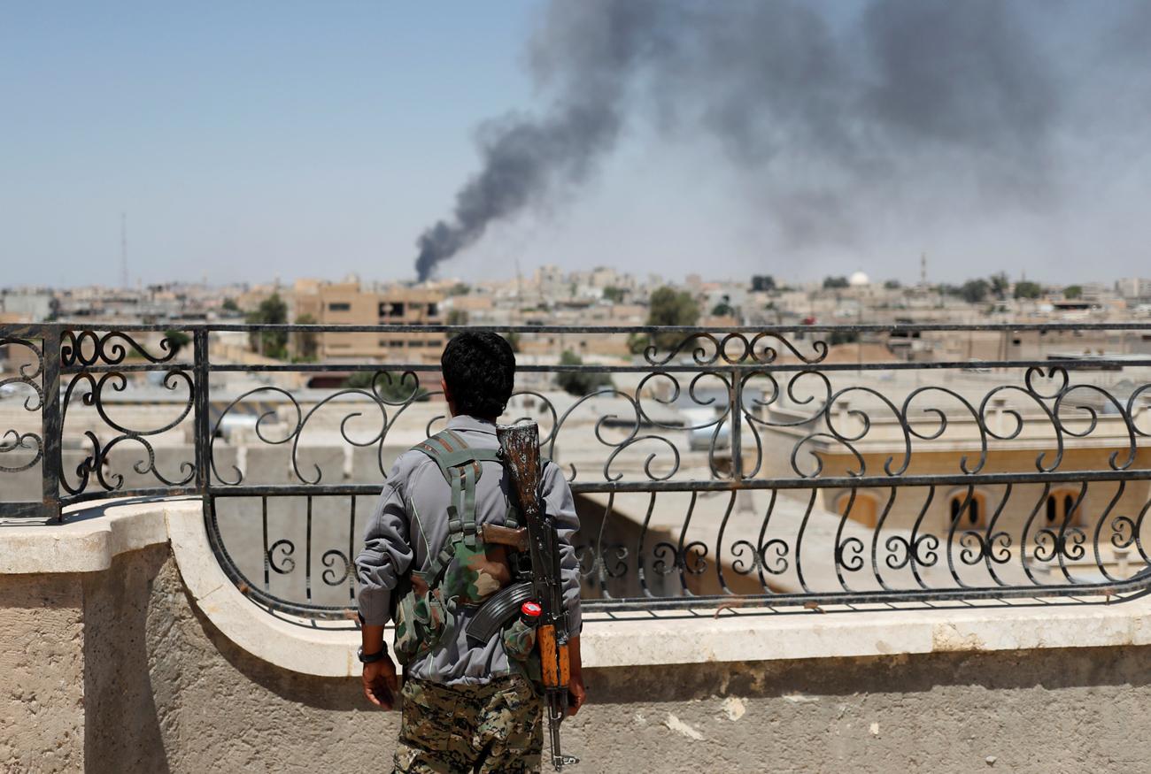 Borec kurdskih Enot za ljudsko zaščito (YPG) gleda dim po koalicijskem napadu na sirsko mesto Raka, 16. junij 2017.