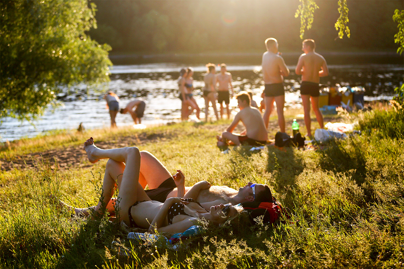 People sunbathing on a beach in Moscow's Serebryany Bor.