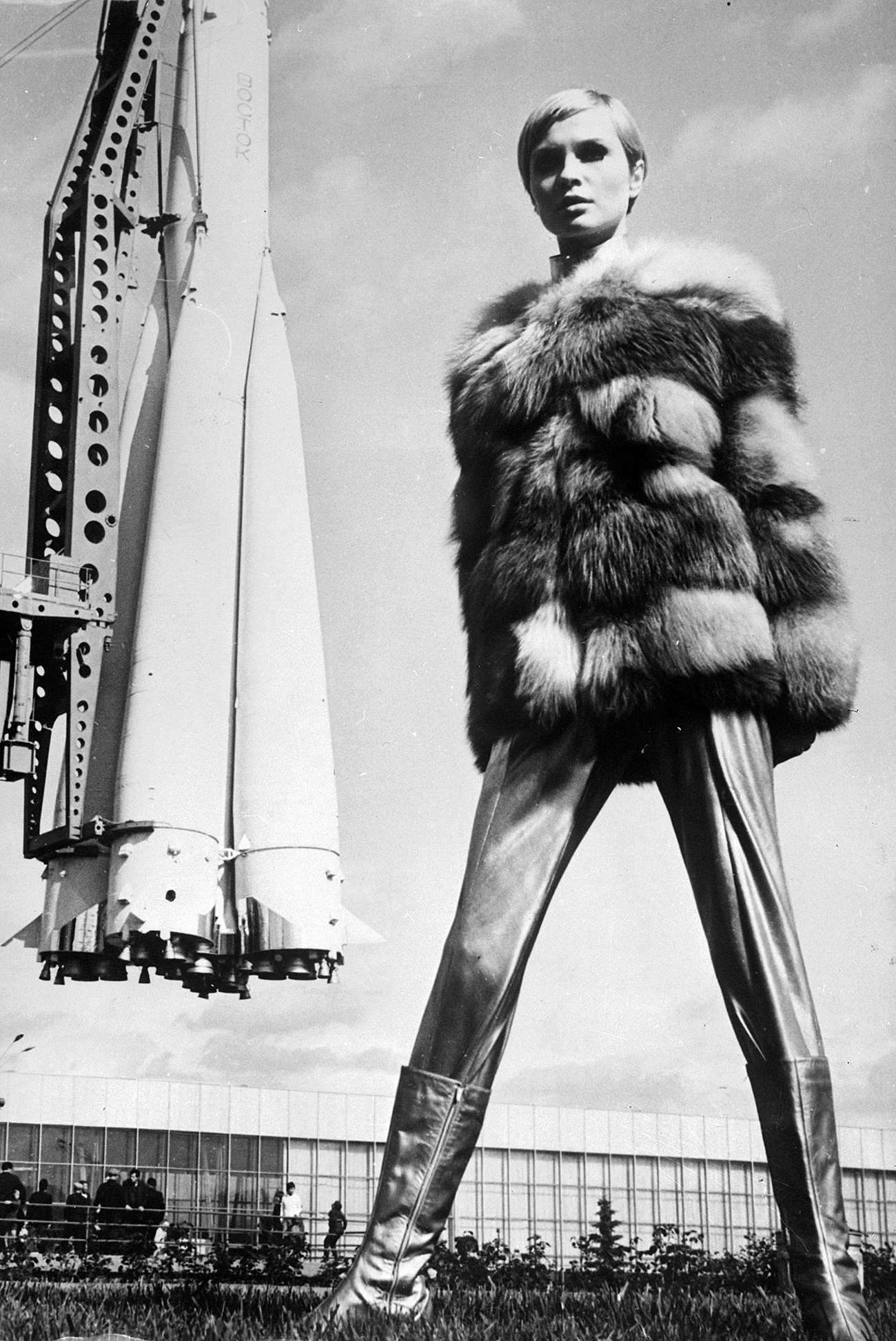 Space-age styling from Russian designers, as Moscovite model Galina Milovskaya wears a metallic ensemble with a red fox fur jacket, leggings and silver boots, the look is completed by the Vostock space rocket in the background. / Getty Images