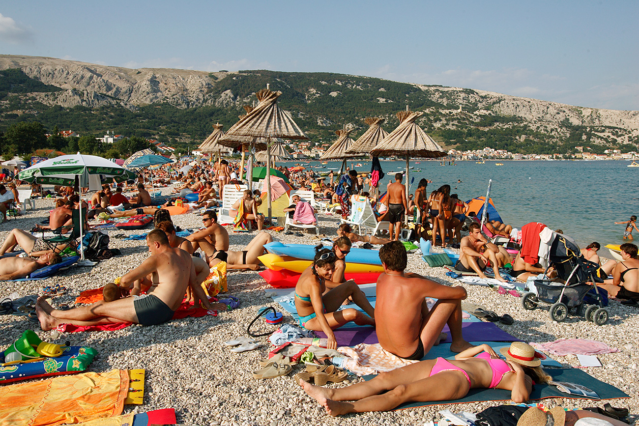 Crowds Sunbathing on Beach on the Adriatic in the town of Baska, on the island of Krk, Croatia.