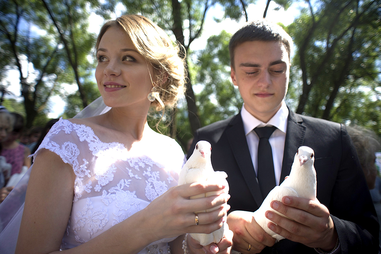 A newly wedded couple holds white doves in their hands at the unveiling ceremony of a monument dedicated to Saint Peter and Saint Fevronia.
