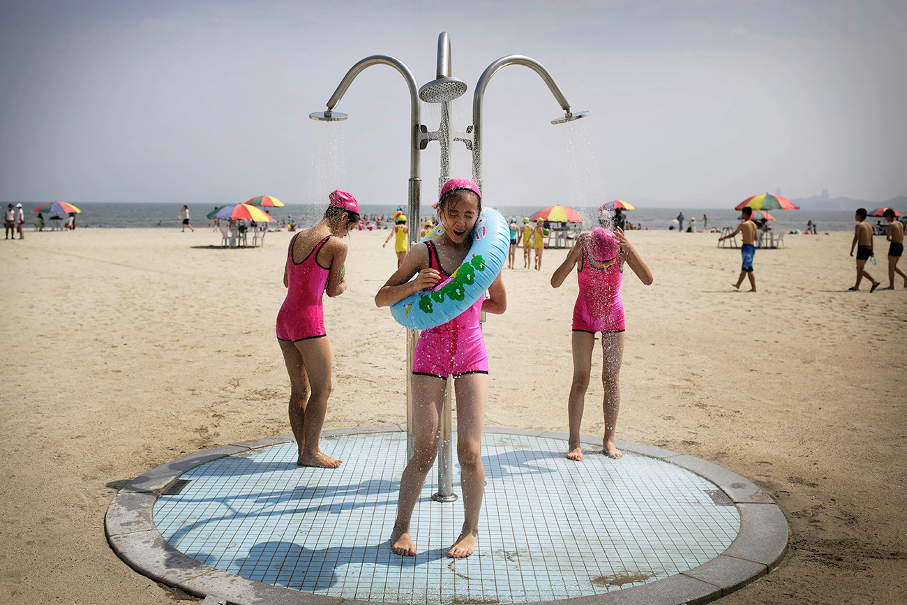 North Korean girls in similar bathing suits stand under a shower at the Songdowon International Children's Camp, Tuesday, July 29, 2014, in Wonsan, North Korea. The camp, which has been operating for nearly 30 years, was originally intended mainly to deepen relations with friendly countries in the Communist or non-aligned world. But officials say they are willing to accept youth from anywhere - even the United States