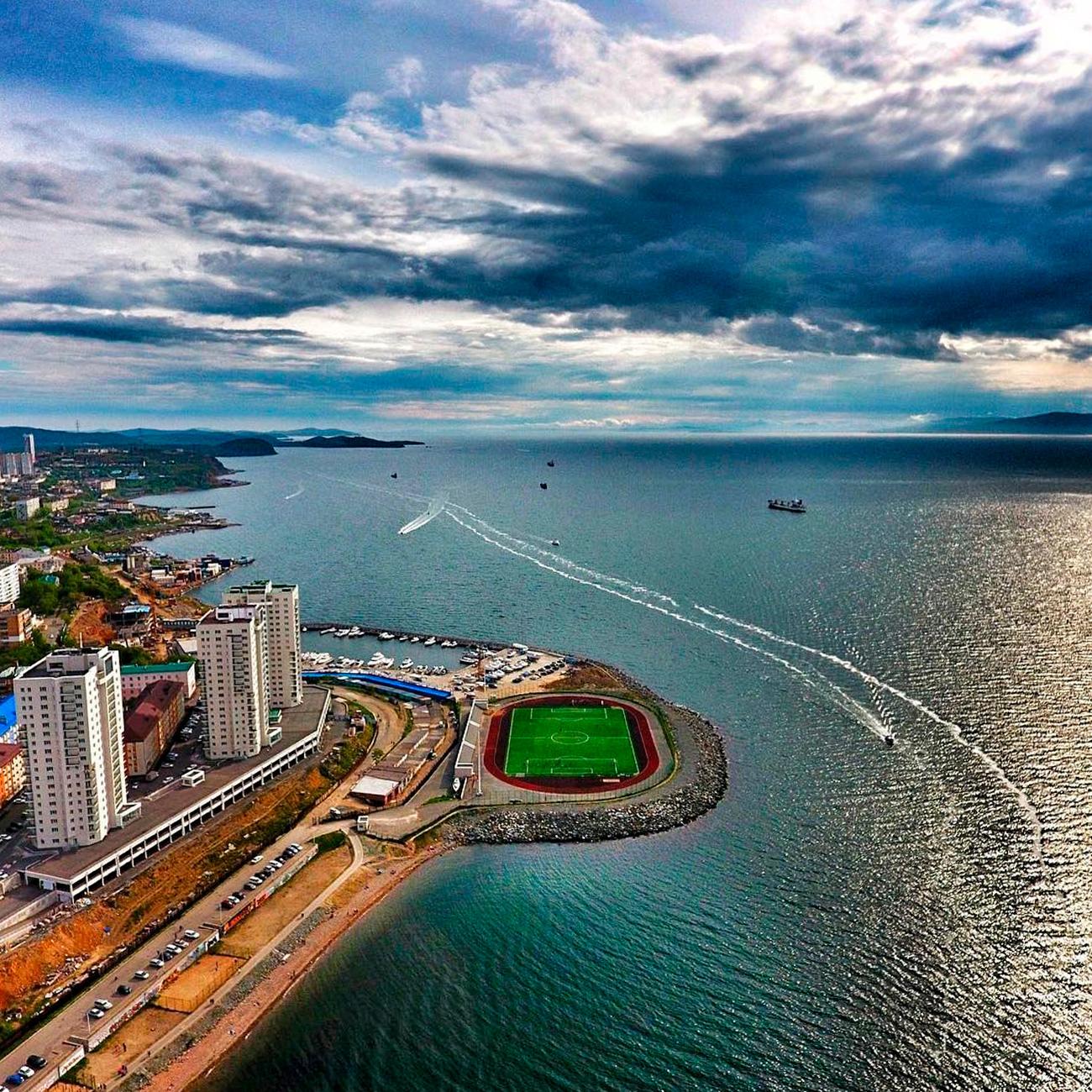 Од птичја перспектива, крајот на заливот Купер кадешто е изграден стадионот, изгледа како блескава зелена точка која ги разграничува водите на заливот Амур од станбениот дел на Владивисток. Стадионот е опкружен со вода од три страни.
