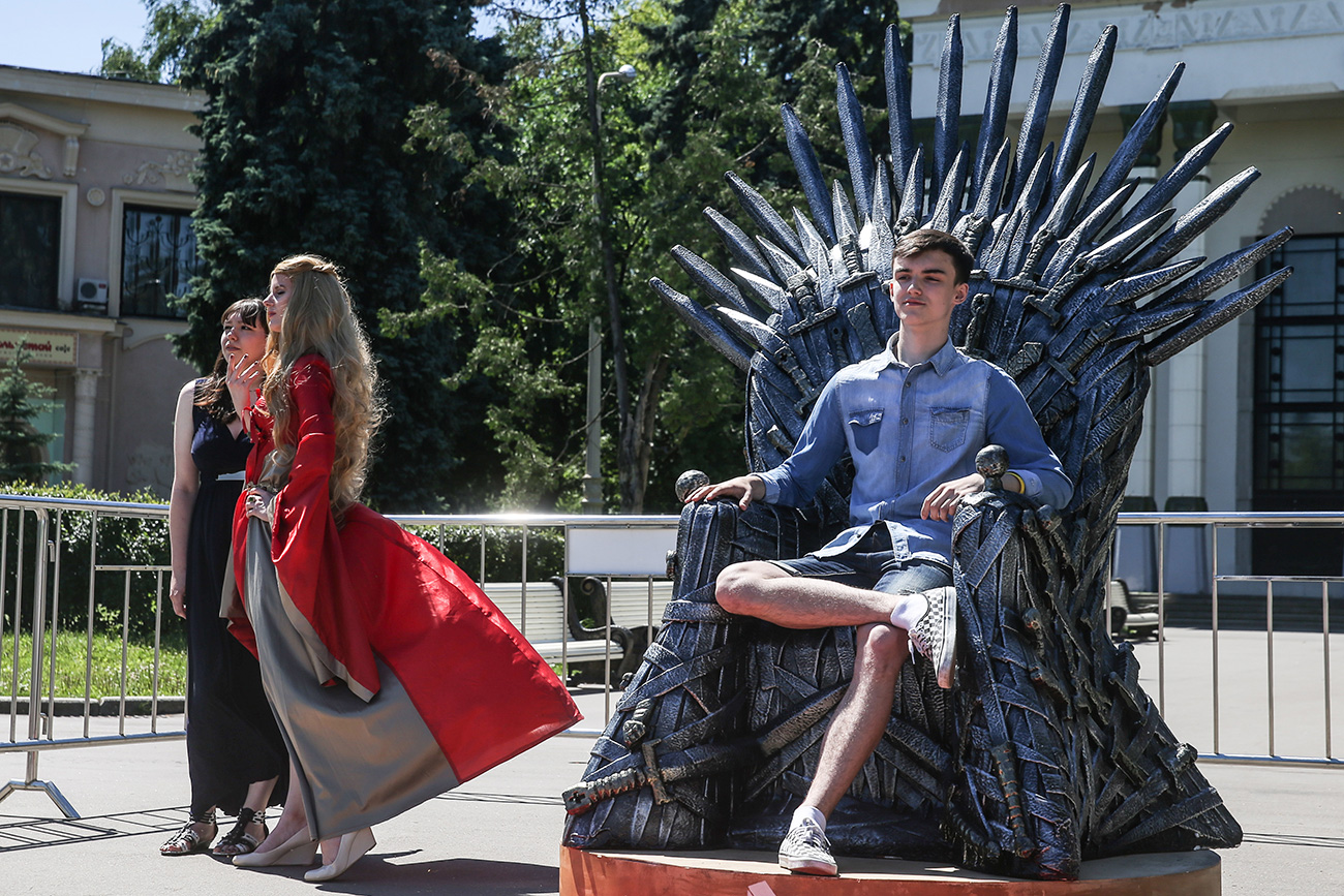 "A young man poses for a photograph on a replica of the throne from the American television series ""Game of Thrones"" based on George R.R. Martin's best-selling book series ""A Song of Ice and Fire"""