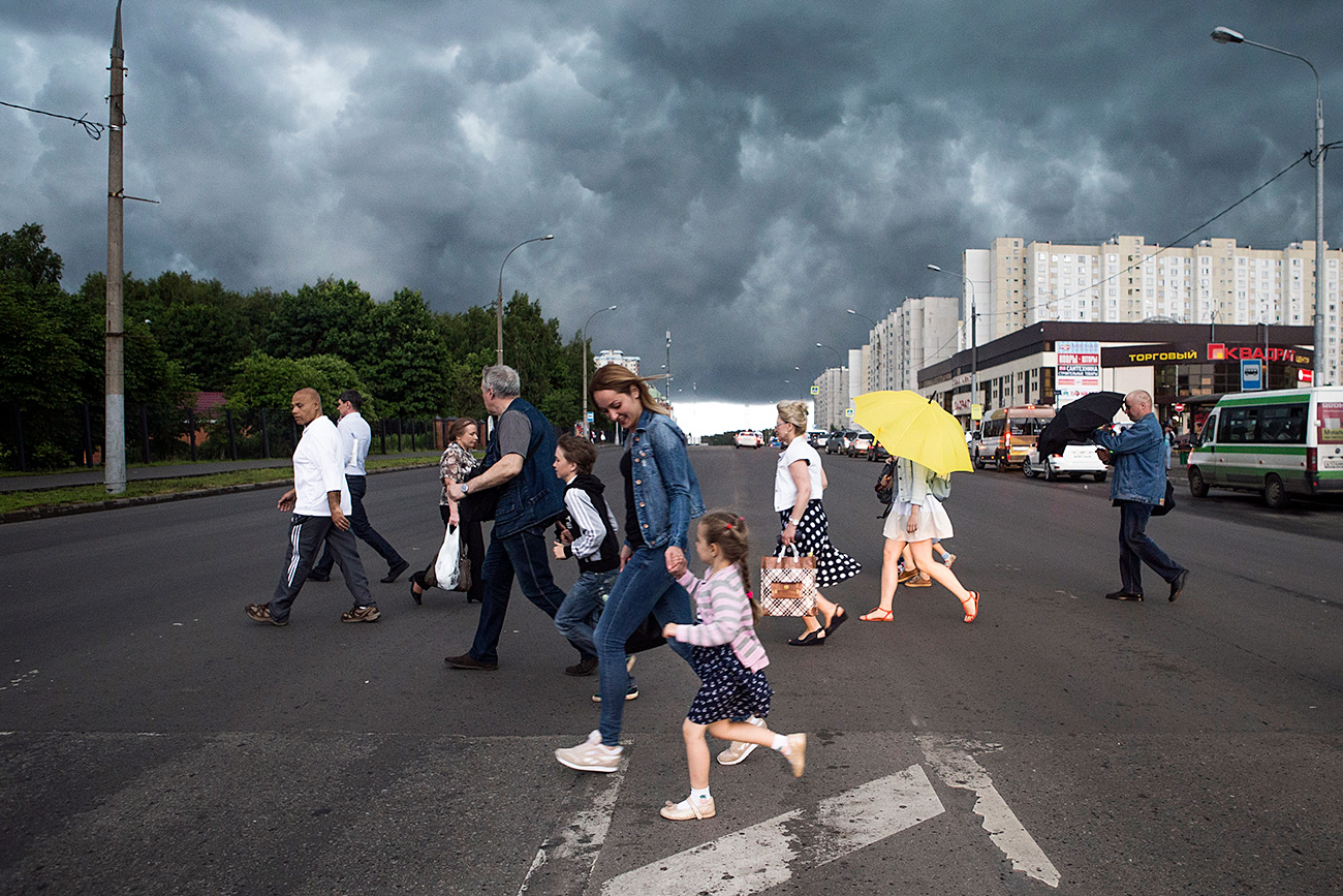 People hurry as they cross a street under a storm cloud in Moscow, Russia, Friday, June 30, 2017. Russian authorities say a massive thunderstorm around Moscow has killed at least one person, injured several others and forced scores of planes to divert to other airports.