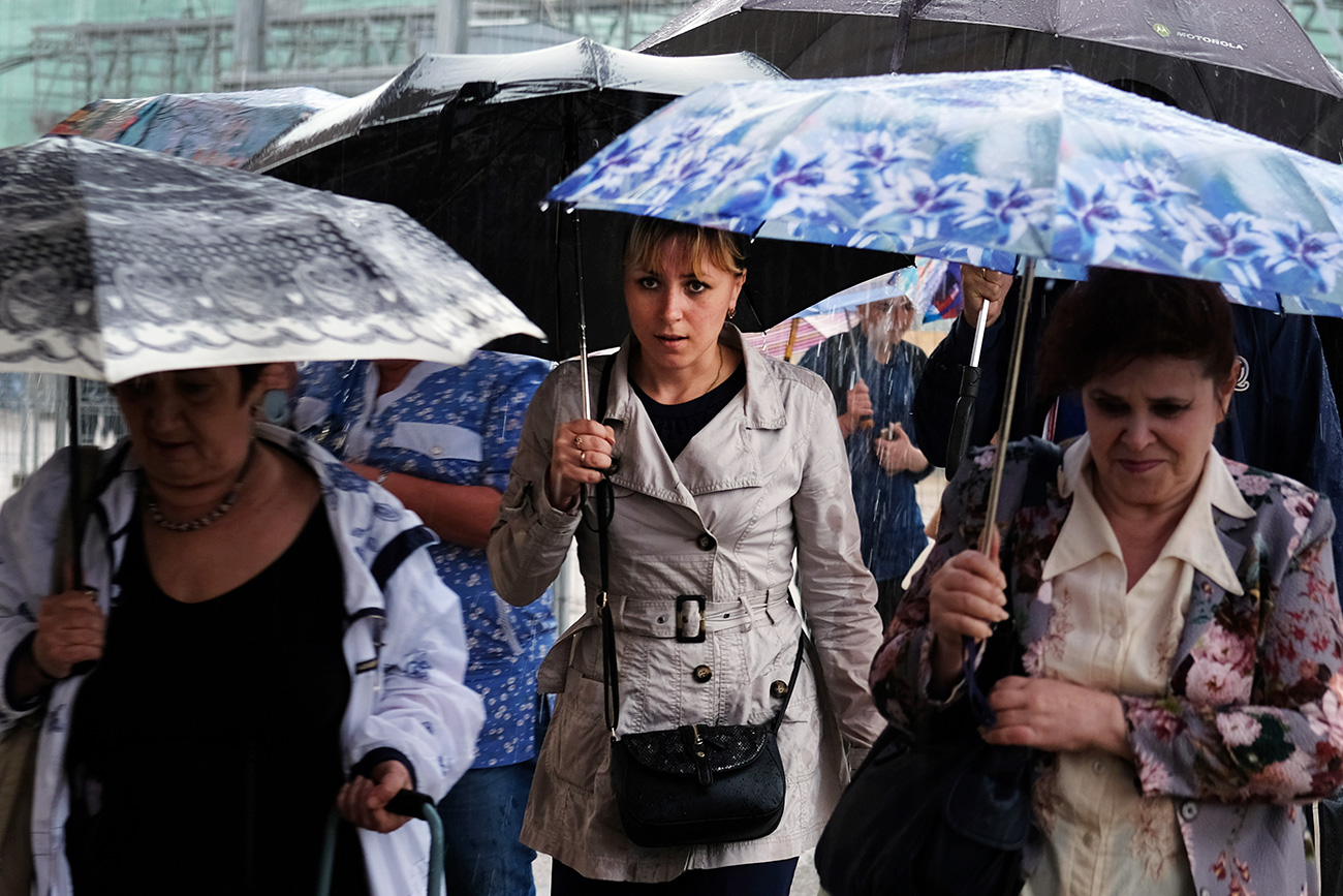 Passers-by in a street of Moscow during a rain.