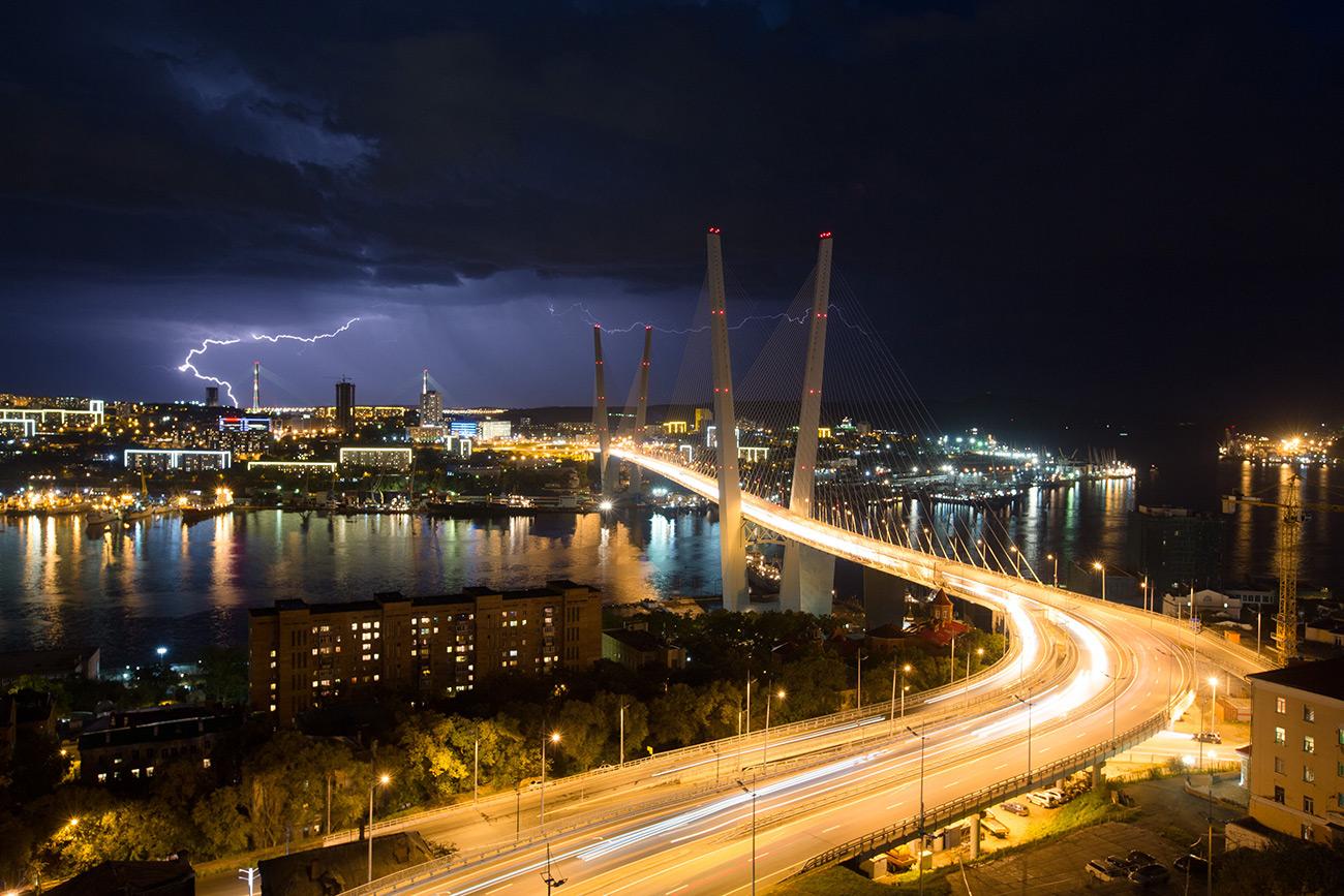 Lightning strikes the city skyline at night beyond the Golden bridge on Golden Horn Bay in Vladivostok\n