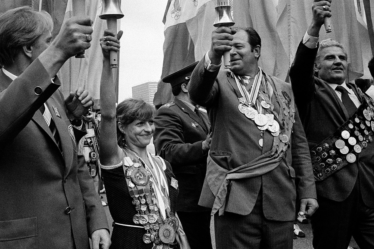 Holding a symbolic Olympic torch, former Soviet gold medalist Olga Korbut, center left, displays her many medals as she celebrates with others the arrival of the official Olympic Flame in Moscow, July 18, 1980. Opening ceremonies for the XXII Summer Olympics are scheduled for tomorrow.
