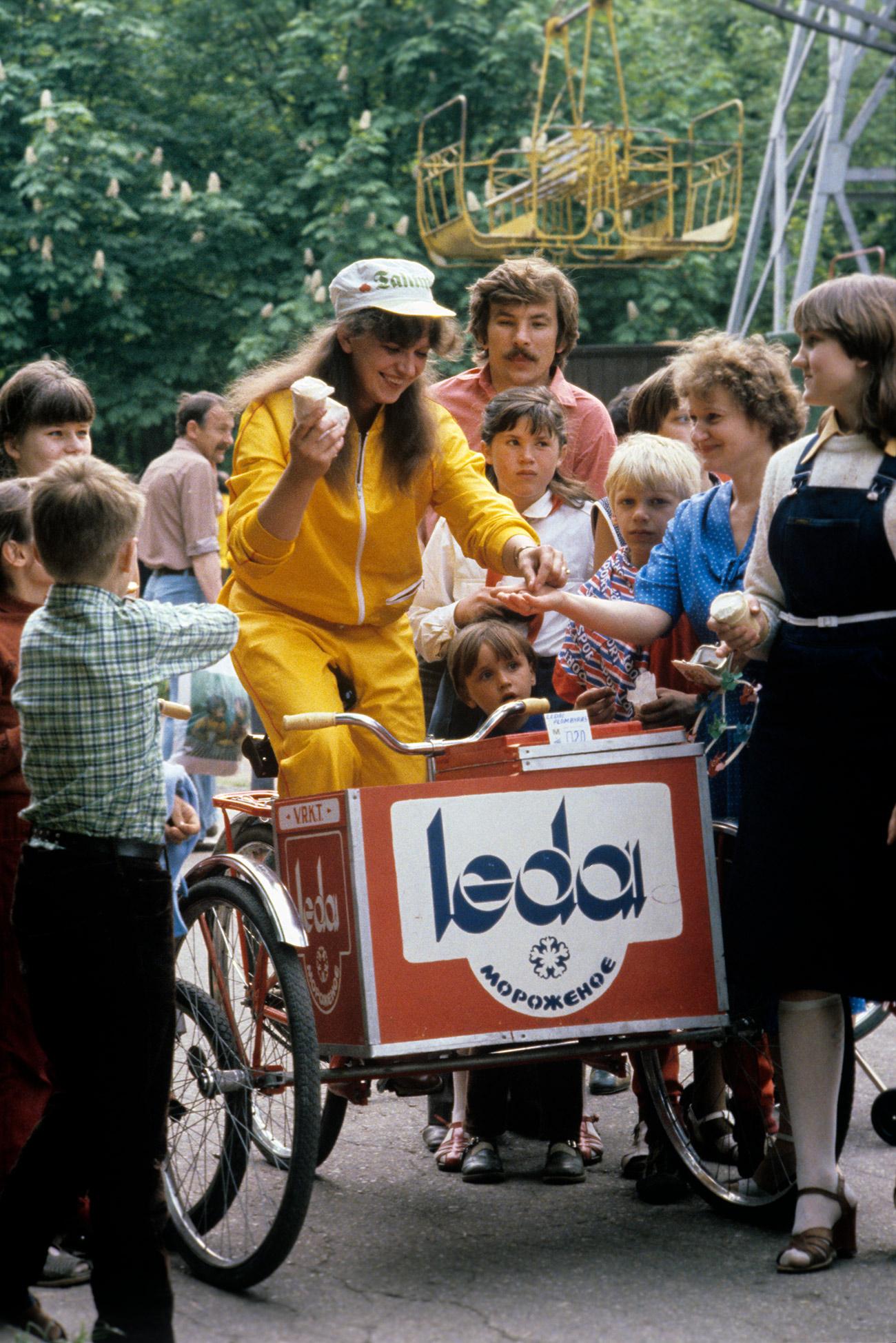 Spesso le persone ne compravano diverse confezioni e correvano a casa per essere sicure che tutti in famiglia ne avessero la propria parte. Donne con in testa un inconfondibile copricapo aprivano il congelatore e permettevano di scegliere il vostro marchio preferito // Carretto dei gelati nel Giorno del Ciclista a Siauliai, Lituania (allora parte dell'Urss), 1983