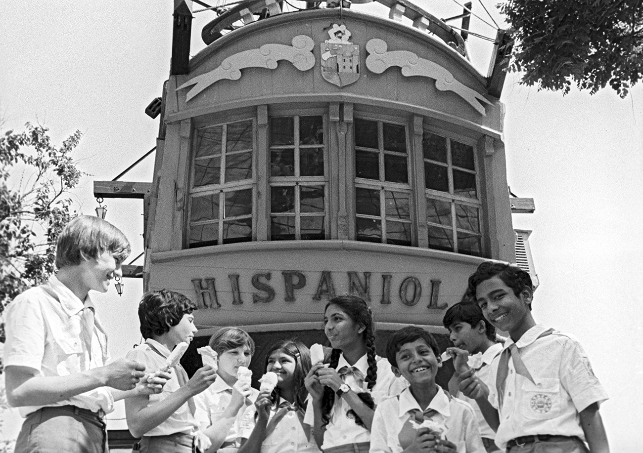 """Il """"lakomka"""" (""""golosone"""") apparve a metà degli anni Settanta e quasi immediatamente divenne una delle varietà di gelato più amate dai bambini sovietici. Era un cilindro di fior di latte o di cioccolato coperto di cioccolato al latte. Costava 28 copeche, l'equivalente, allora, di nove corse in tram // Ragazzi si riposano e mangiano un gelato all'Artek, un campo estivo dei """"Pionieri"""" in Crimea, 1980"""