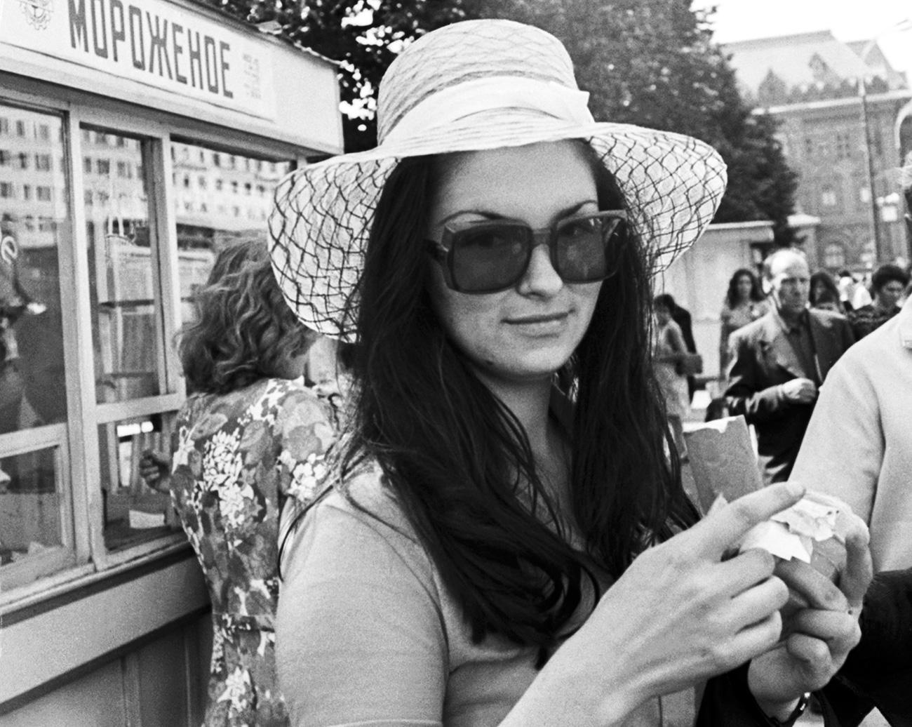 """Il più caro tra i gelati sovietici (48 copeche) era il fior di latte """"Plombir"""". Pesava 250 grammi, ma questa porzione non era abbastanza per l'intera famiglia. I sovietici lo amavano ricoperto di marmellata fatta in casa (in russo, varenje) // La turista bulgara Anja Kapitanova mangia un gelato nel centro di Mosca, 1976"""