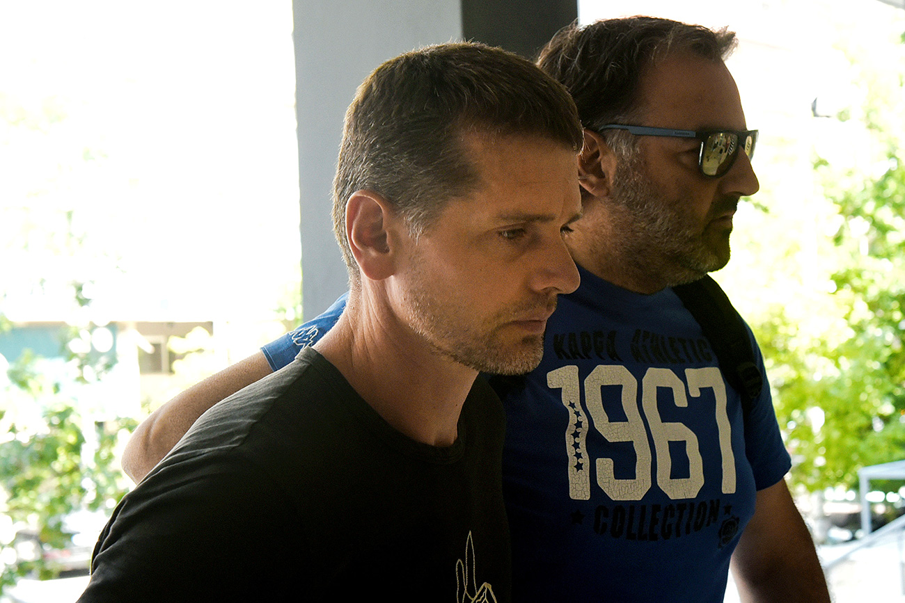 Alexander Vinnik, suspected of running a money laundering operation, is escorted by a plain-clothes police officer to a court in Thessaloniki, July 26, 2017.  / Reuters