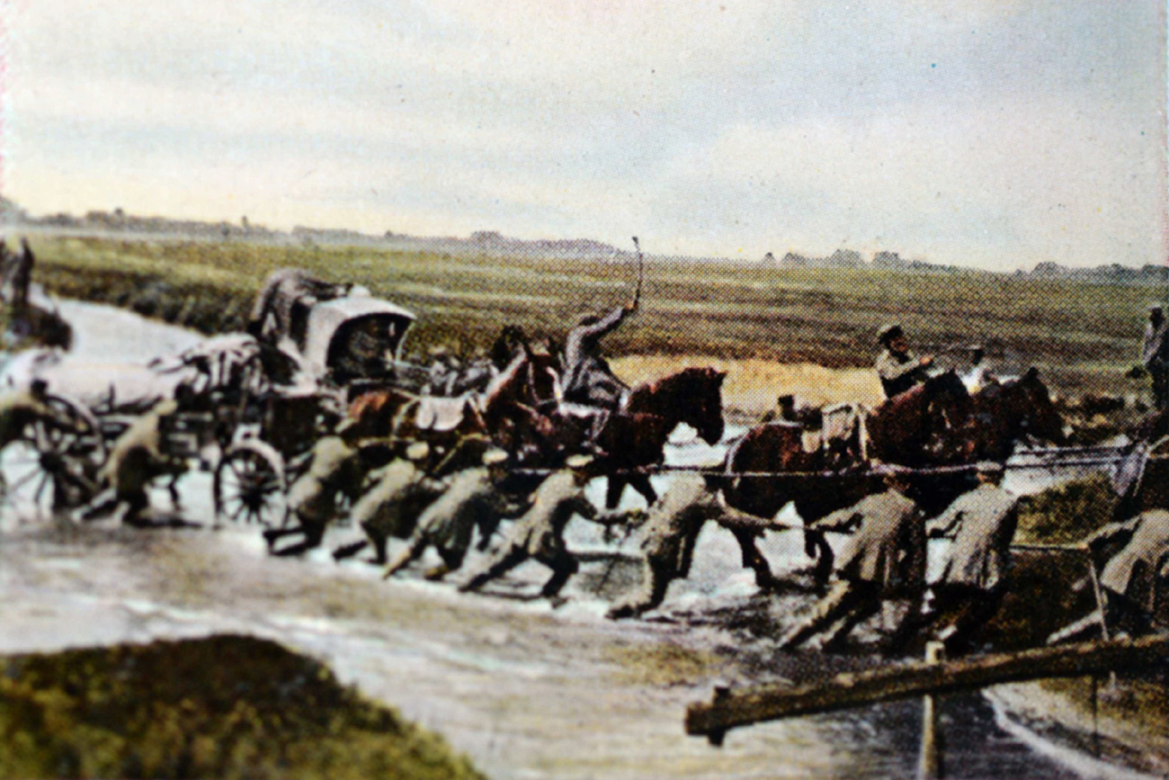 The contemporary colorized German propaganda photo shows German troops crossing a river on the Eastern Front in 1916.