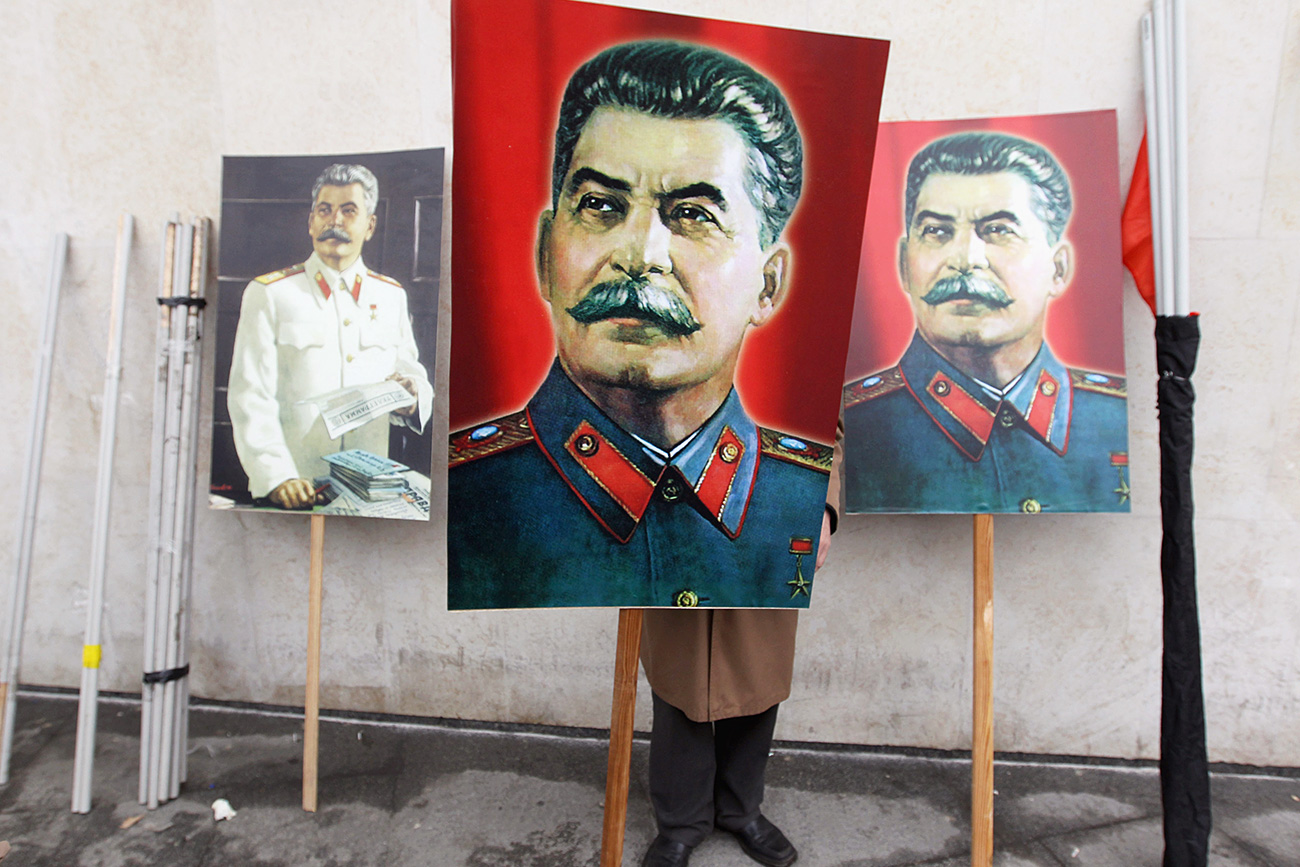 A communist supporter holds a portrait of Joseph Stalin.