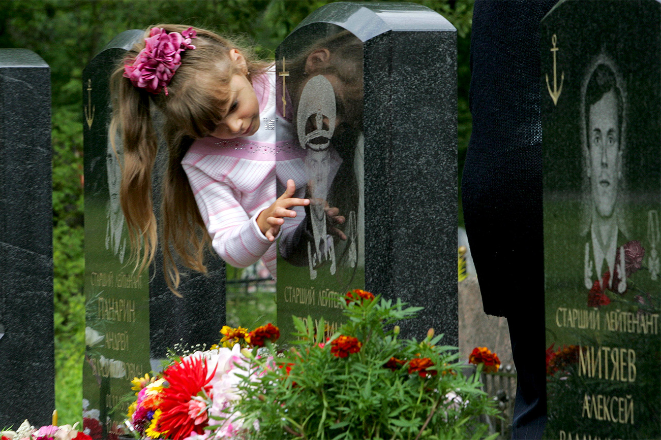 Seven-year-old Kristina Yerakhtina touches the tombstone of her father Sergei Yerakhtin Kursk nuclear submarine's officer at Serafimovskoye cemetery in St.Petersburg. Seven-year-old Kristina Yerakhtina touches the tombstone of her father Sergei Yerakhtin, Kursk nuclear submarine's officer, at Serafimovskoye cemetery in St.Petersburg, August 12, 2005. Russia marks five years since the loss of 118 sailors when the nuclear submarine Kursk went down in the Barents Sea after a torpedo exploded on board.