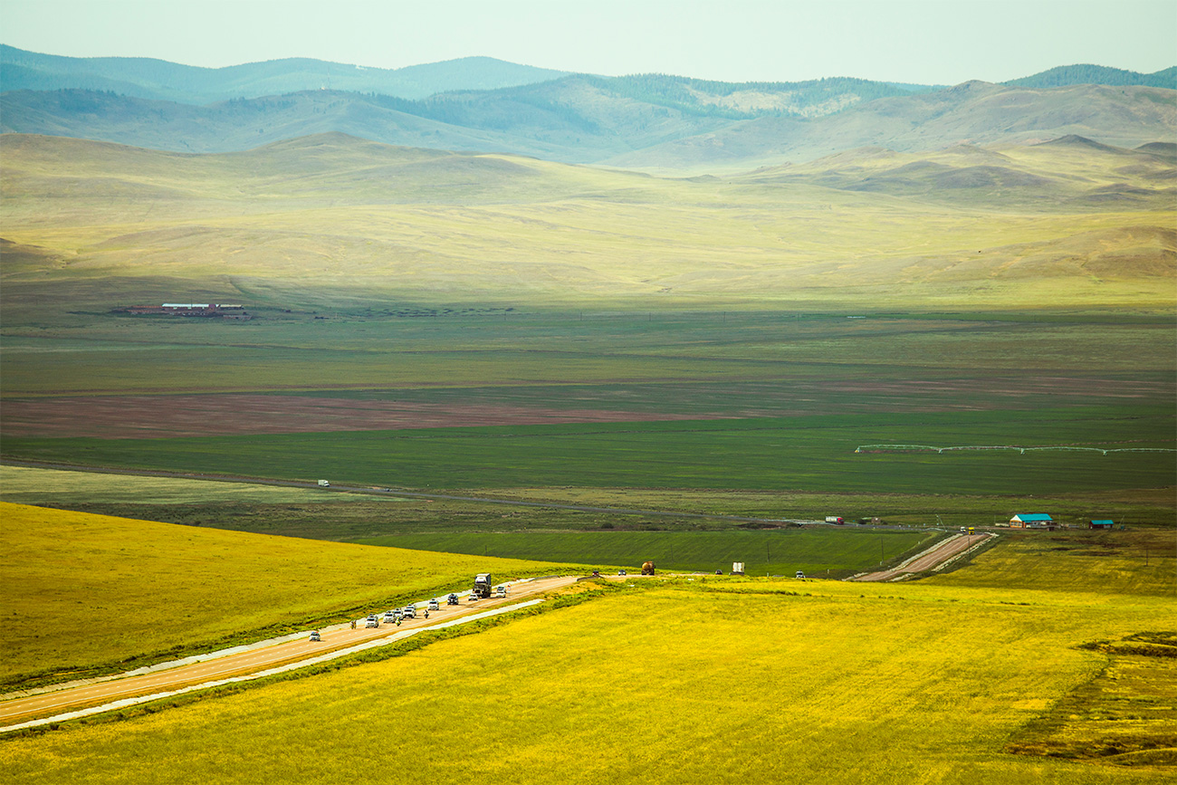 Can you imagine seeing all those remote places and unbelievable landscapes not from the train window, but having a chance to stop and touch the ground and pick a flower? In the picture you can see the Ulan-Ude to Chita stage. Lake Baikal is behind the cyclists' shoulders.