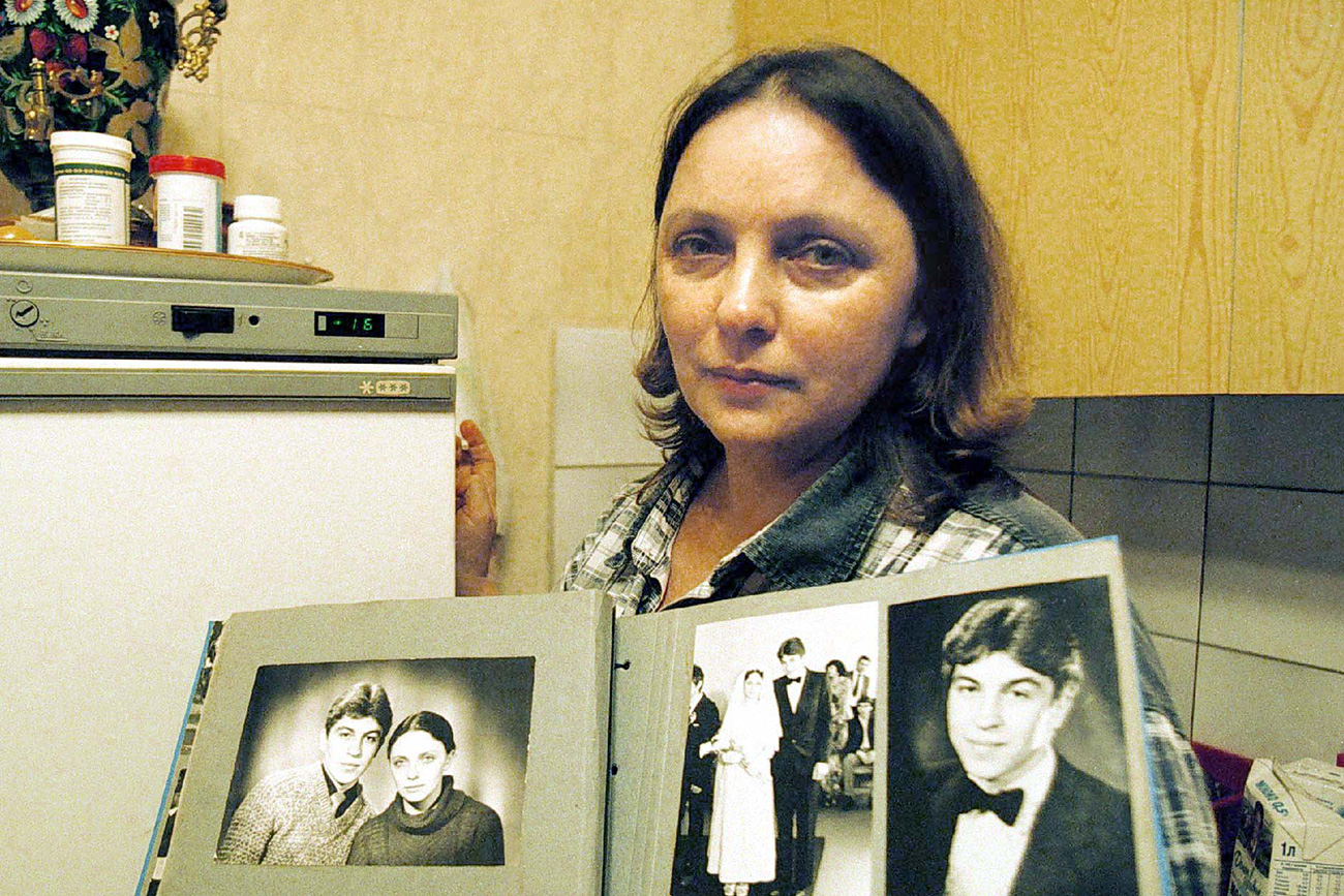 Larisa Savitskaya, the sole survivor of a 1981 mid-air plane collision, holds old photos of herself and her husband, Moscow, 2001.
