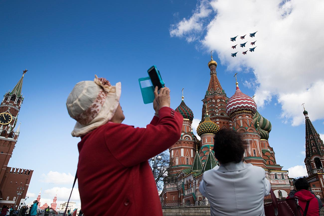 Wisatawan mengambil foto jet-jet tempur Rusia yang terbang melintasi Kremlin.