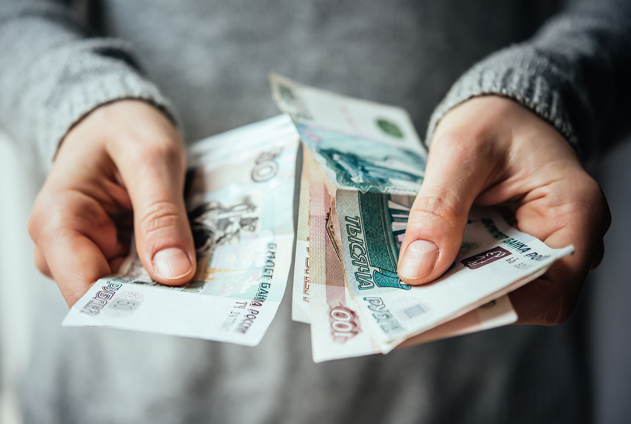 Hands holding russian rouble bills